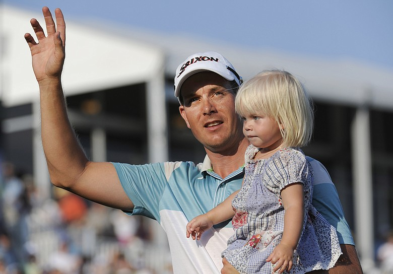 Henrik Stenson celebrates with his daughter, Lisa, leaving the 18th green after winning the Players Championship.