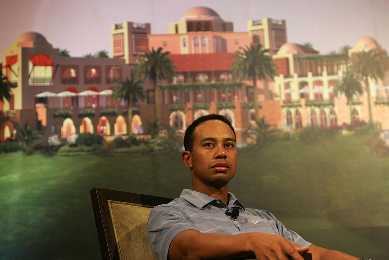 Tiger Woods in front of a poster showing the planned development of the Tiger Woods Dubai community at a venue in Dubai.