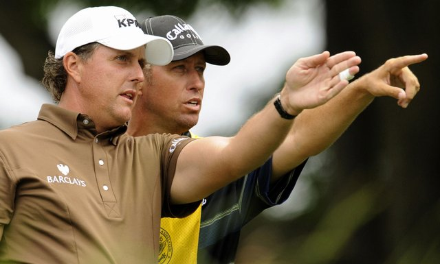 Phil Mickelson of the US and his caddie Jim Mackay discuss a shot during the final round of the U.S. Open.