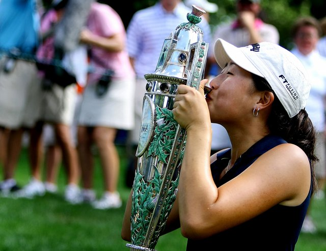 Jennifer Song kisses the Robert Cox Cup on the 17th green were she was presented with the trophy after winning the 109th U. S. Women's Amateur Championship.