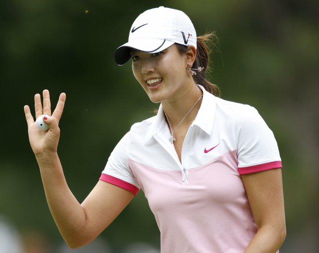 Michelle Wie waves to fans after making a birdie on the 17th hole during the second round of the Jamie Farr Owens Corning Classic.