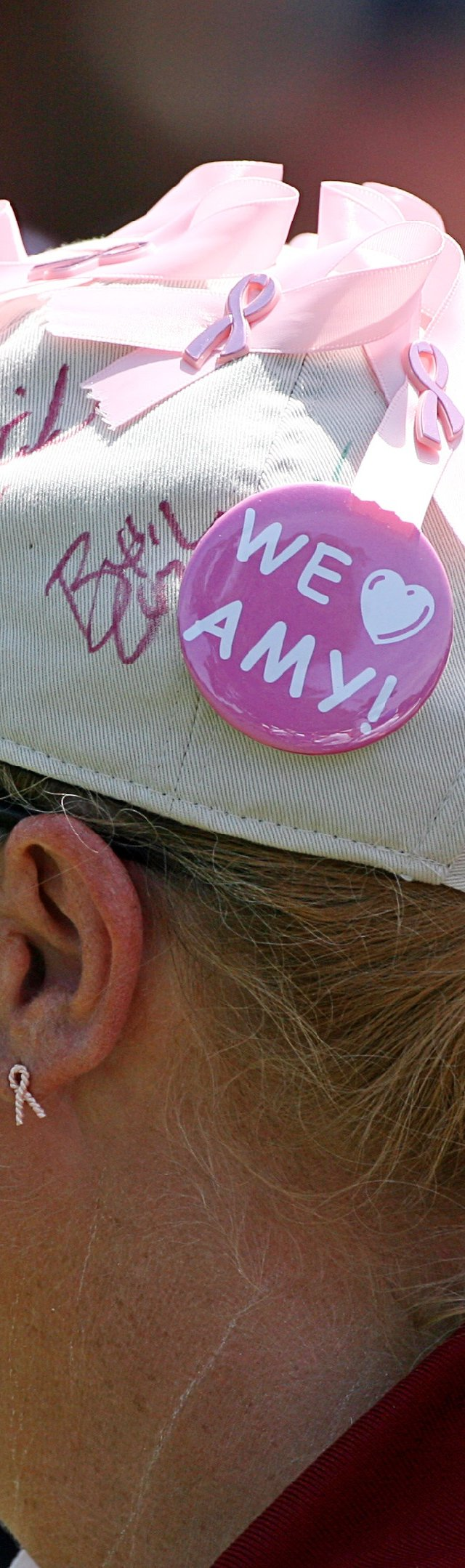 A tournament volunteer wears pink ribbons and a &#39;We Love Amy&#39; button on her hat to show her support for Amy Mickelson and breast cancer research during the third round of the Crowne Plaza Invitational at Colonial Country Club.