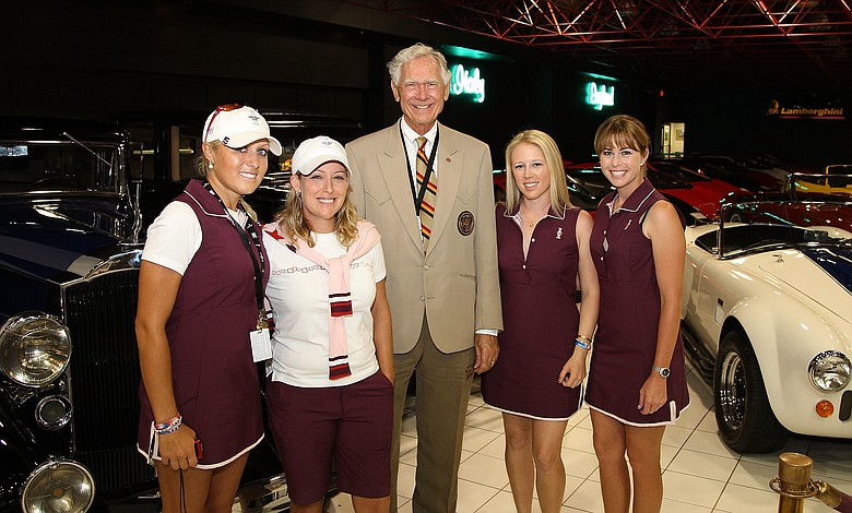 Jerry Rich, owner of the Rich Harvest Farms, poses with (L-R) Natalie Gulbis, Cristie Kerr, Morgan Pressel and Paula Creamer of the U.S. Solheim team inside the car museum on the grounds of Rich Harvest Farms.