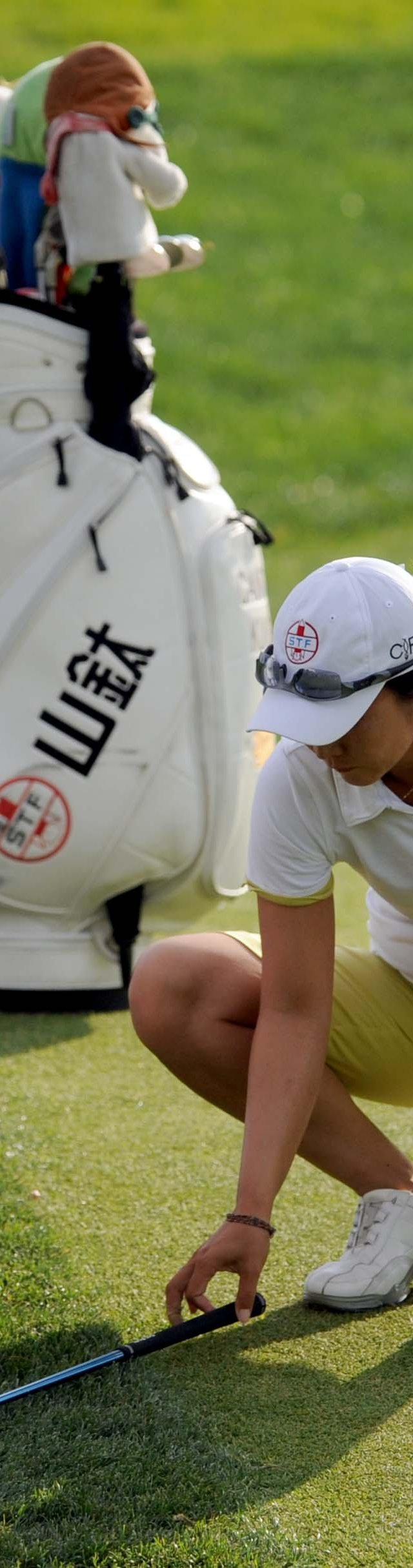 Candie Kung and her caddie Jeff King measure for relief under a special rule for the step-cut rough during the first round of the Safeway Classic.