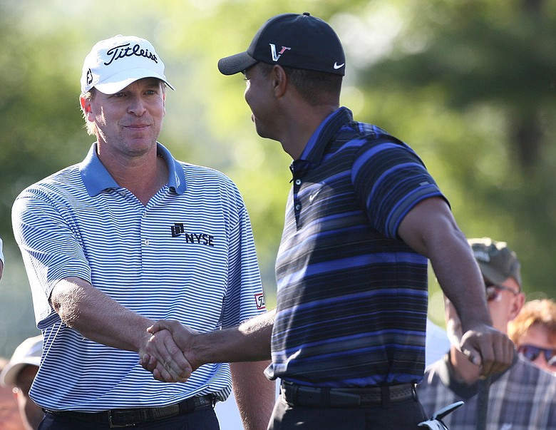 Tiger Woods shakes hands with Steve Stricker during Round 1 of the 2009 Deutsche Bank Championship In Norton, Mass. on Sept. 4, 2009.