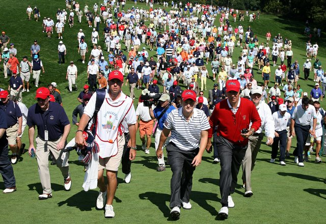 Bud Cauley and captain Buddy Marucci walk ahead of the huge gallery at the 18th hole on Sept. 13.