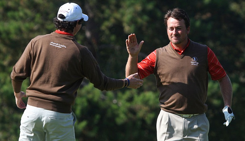 Graeme McDowell, right, reacts with Great Britain and Ireland teammate Rory McIlroy, after holing out for birdie out of a bunker at the 16th hole.