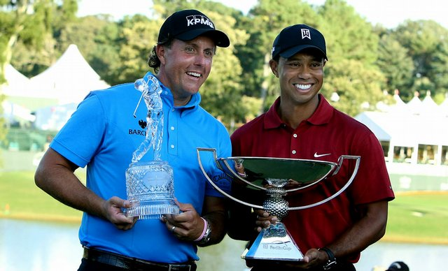 Phil Mickelson and Tiger Woods pose with their prizes.