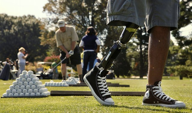 Army Staff Sgt. Alfredo de los Santos, right, a patient at Walter Reed Army Medical Center, swivels while practicing his golf swing at Woodmont Country Club in Rockville, Md., as part of the Wounded Warrior Project.