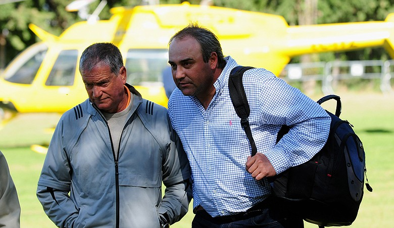 Angel Cabrera is greeted by Victor Garcia, Sergio Garcia's father, after his helicopter was delayed due to strong winds. Cabrera was  disqualified for missing his tee time.