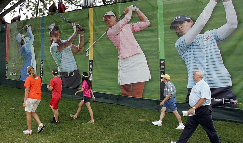 Fans walk past posters of Natalie Gulbis, Lorena Ochoa, Paula Creamer and Juli Inkster at an LPGA event. The tour plans to showcase its top stars at a new tournament this fall in Malaysia.