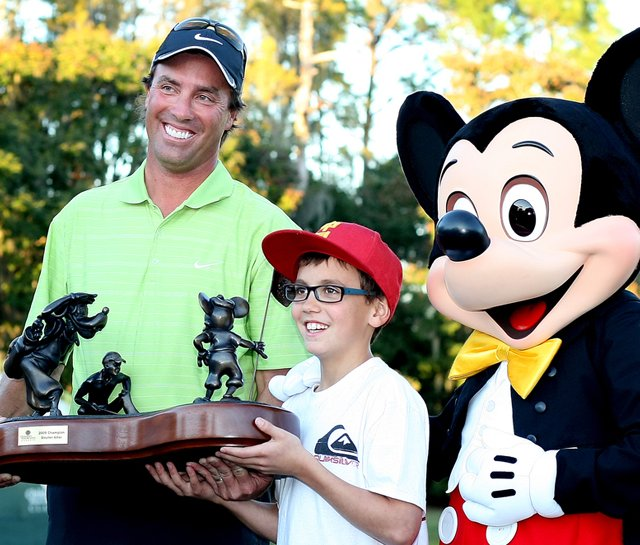 Stephen Ames holds the championship trophy with son, Ryan, 10, and Mickey Mouse after winning the Children&#39;s Miracle Network Classic on Nov. 15.