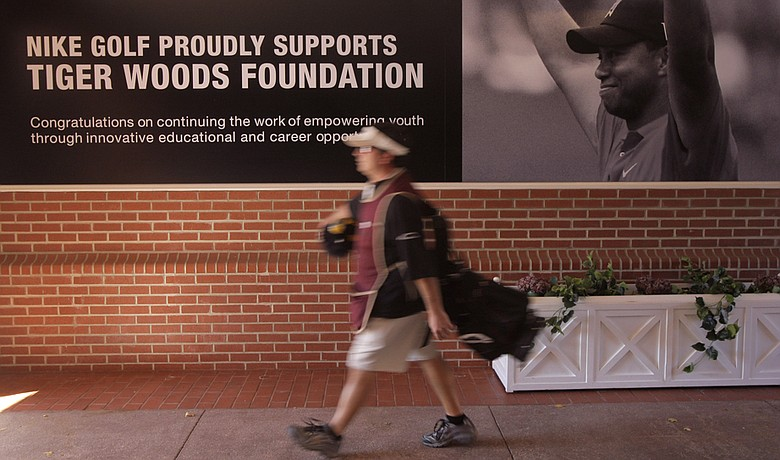 A caddie walks past an advertisement showing a photo of Tiger Woods at Sherwood Country Club in Thousand Oaks, Calif., The Chevron World Challenge, which benefits the Tiger Woods Foundation, will take place at Sherwood this week. Woods will not attend.