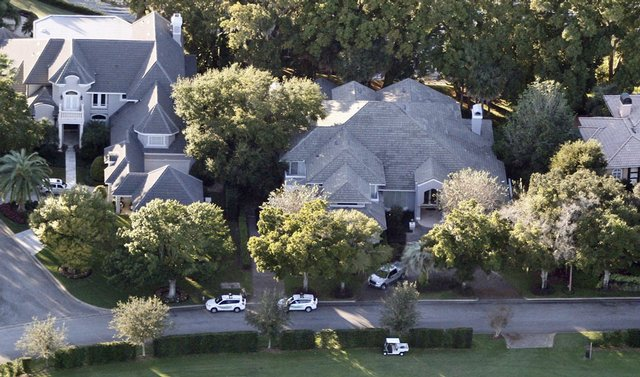Security guards gather near the home, left, of Tiger Woods in Windermere, Fla.