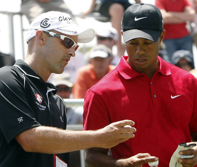Cameron Percy checks balls with Tiger Woods during the final round of the Australian Masters.