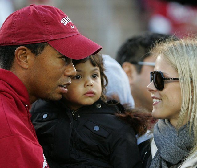 Tiger Woods holds his daugher, Sam, and speaks to his wife, Elin, on the sidelines before the Stanford Cardinal football game against California on Nov. 21.