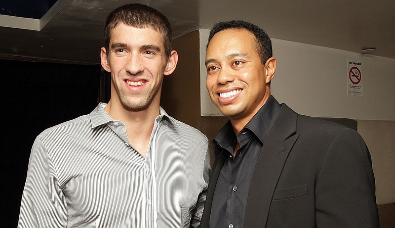 Michael Phelps and Tiger Woods pose for a photo during the Tiger Woods Video Game Launch Party at Strata Metronome New York City.