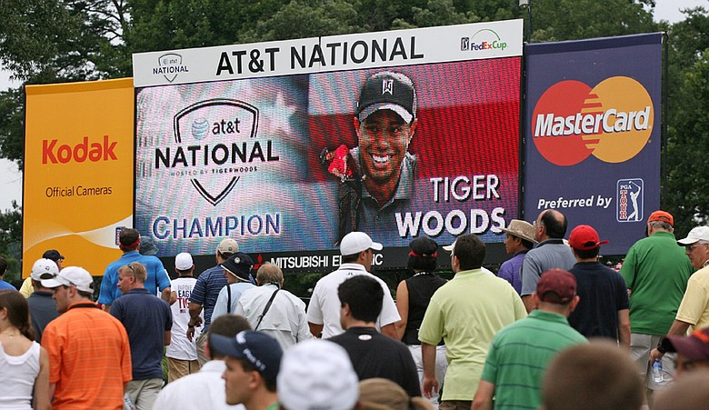Fans walk by a scoreboard as they leave the course after the final round of the AT&T National hosted by Tiger Woods.