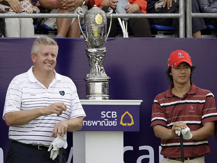 Colin Montgomerie, left, and Ryo Ishikawa stand beside Royal Trophy before facing off in their opening foursomes match.