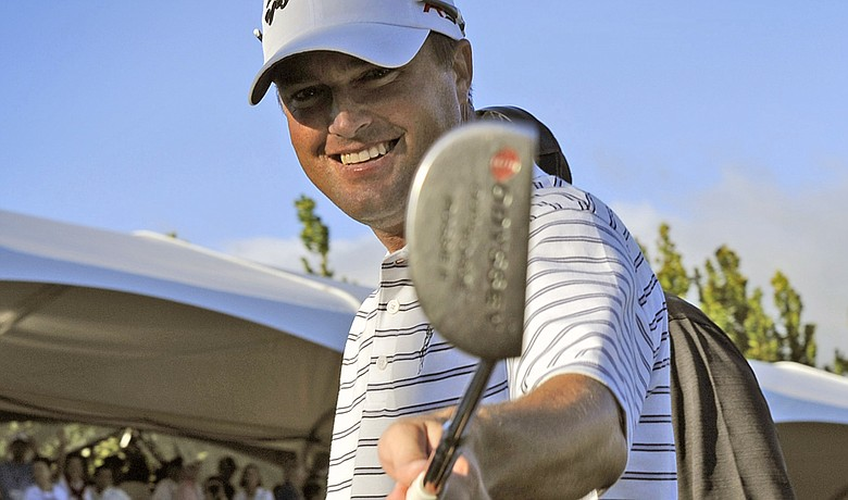 Ryan Palmer waves his putter as he exits the 18th green winning the Sony Open.
