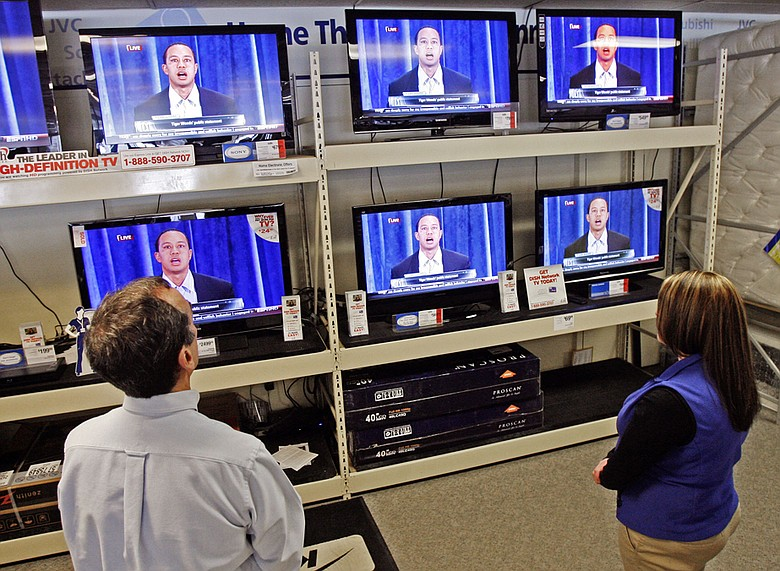 Employees watch Tiger Woods on television at a Sears store in Berlin, Vt., on Feb. 19.