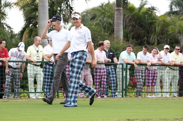 Ian Poulter reacts to similarly dressed fans.