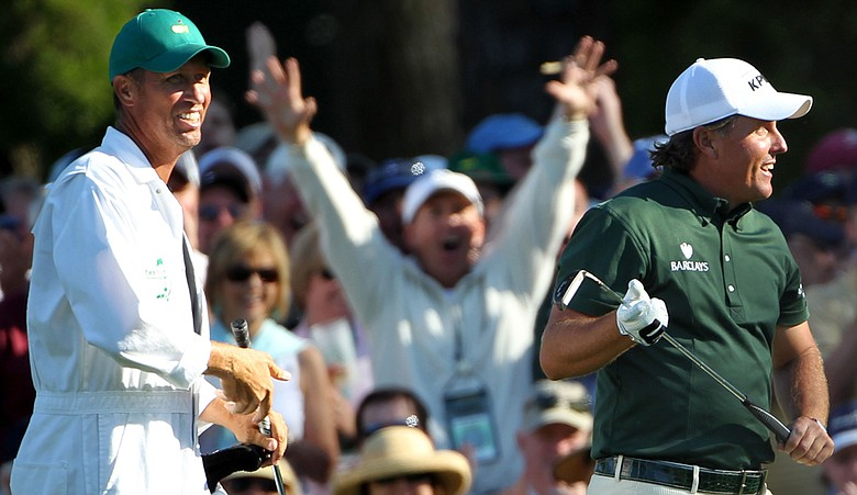 Phil Mickelson takes his putter from his caddie Jim Mackay on the 15th hole as a patron celebrates in the gallery during Round 3.