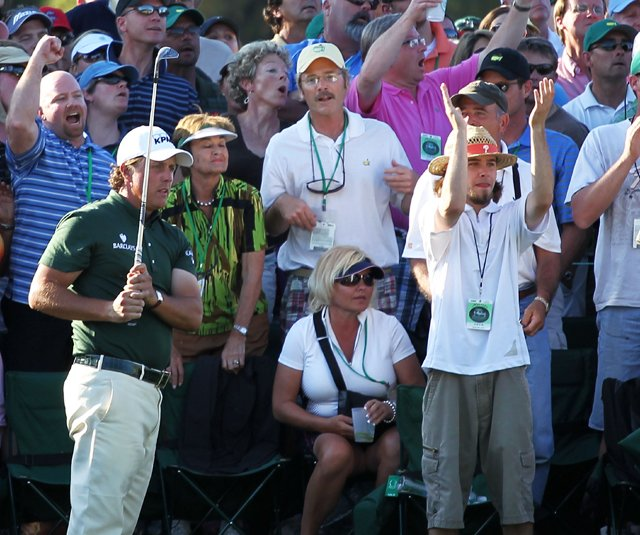 Phil Mickelson hits a pitch shot to the 18th green during the third round of the Masters amid a crowd of patrons.