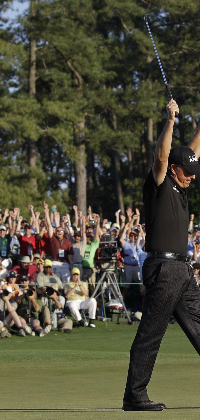 Phil Mickelson celebrates on the 18th green after making birdie and winning his third Masters by three shots.