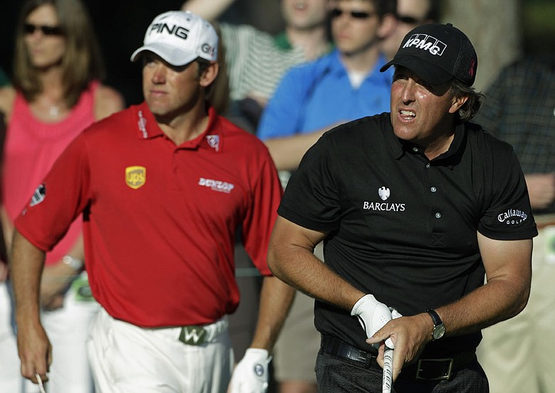 Phil Mickelson and Lee Westwood watch Mickelson's tee shot on the 15th hole during the final round of the Masters.