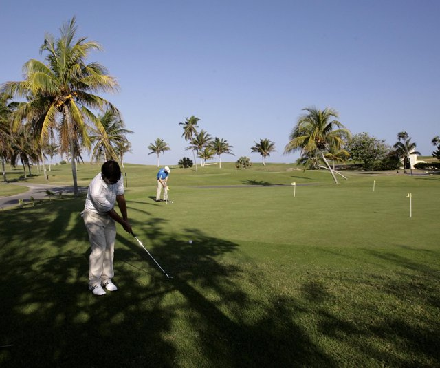 Players hit the practice green during the Montecristo Cup Golf Tournament in Varadero, Cuba