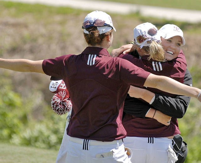 Texas A&amp;M junior Sarah Zwartynski is hugged by her teammates after sinking the putt to win the Big 12 Championship.