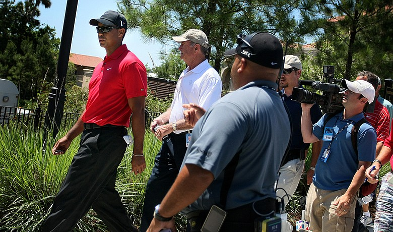 Tiger Woods walks off the course after withdrawing from The Players Championship on May 9.