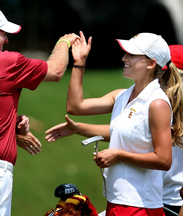 USC’s director of golf, Kurt Schuette (left) high-fives Belen Mozo after her second-round 72.