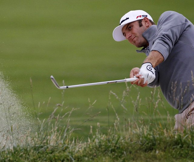 Dustin Johnson hits out of a bunker at the lengthened 15th hole at Pebble Beach.