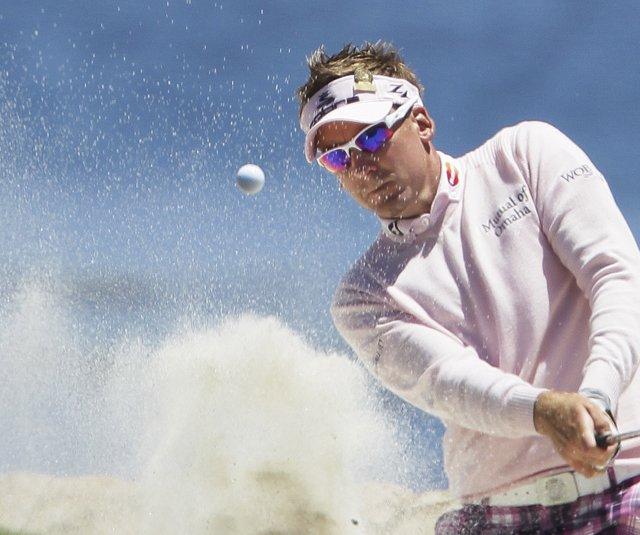 Ian Poulter blasts out of a bunker at the 18th.