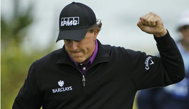 Phil Mickelson pumps a fist on his way to a second-round 66.