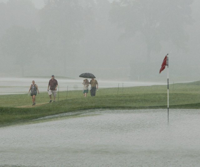 Fans walk past the saturated ninth green at Oakmont as storms suspend Round 2 of the U.S. Women&#39;s Open.