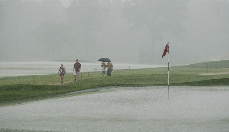 Fans walk past the saturated ninth green at Oakmont as storms suspend Round 2 of the U.S. Women's Open.