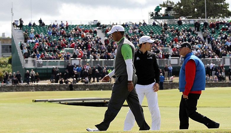 Tiger Woods walks back up the first fairway after play was suspended during Round 2 of the British Open.