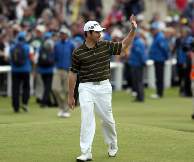 Louis Oosthuizen waves to the crowd as he walks down the 18th fairway during the final round of the British Open.