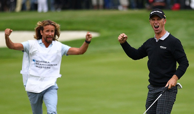Richard S. Johnson celebrates with caddie, Anders Timell, after making birdie on No. 18 to win the Scandinavian Masters by a shot.