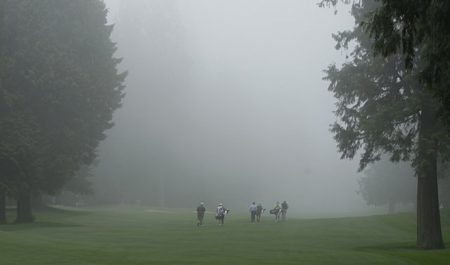 Golfers, from left, Larry Stubblefield, Bill Britton, and Jon Fiedler, and their caddies, walk into the fog on the 1st fairway during the second round of the U.S. Senior Open.