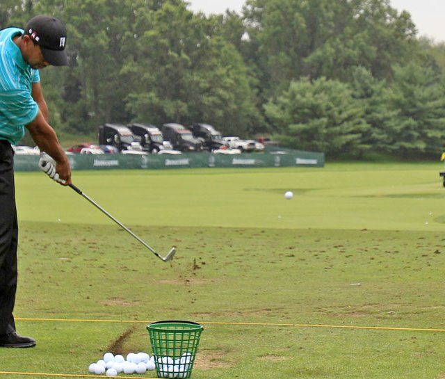 Tiger Woods hits balls on the practice range at the Bridgestone Invitational.