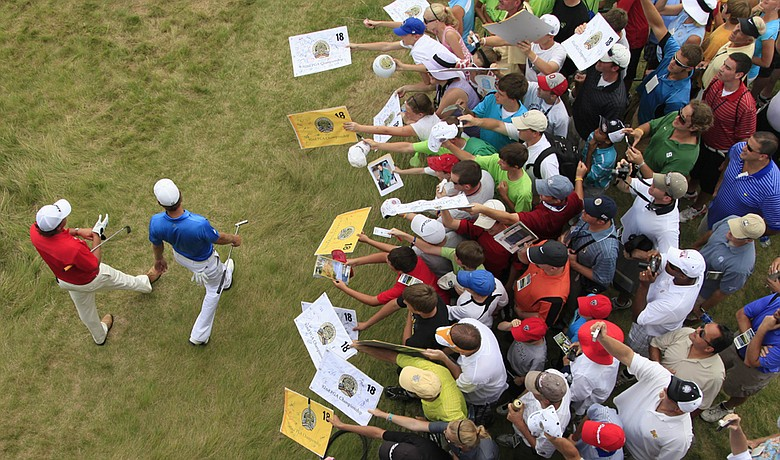 Phil Mickelson (left) and Dustin Johnson make their way to the 17th hole as fans try to get an autographs during a practice round for the PGA Championship.