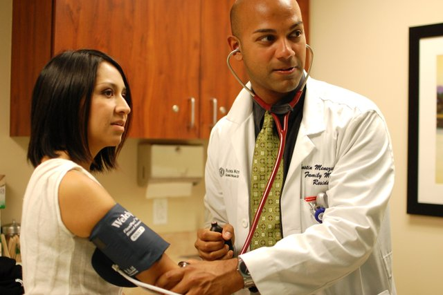 Residents Paulina Castro, left, and Justin Menezes practice taking each other's blood pressure.