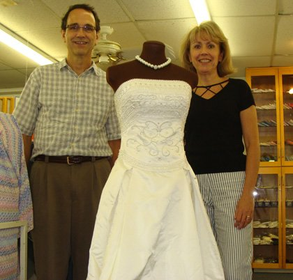 Sewing Studio owners Pat and Mark Sauer stand next to Kim McGauley&#39;s handmade wedding dress displayed in the store.