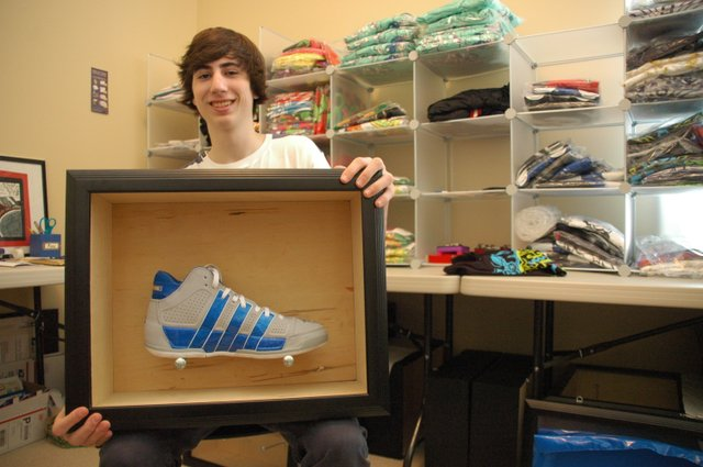 Corey Kamenoff, 16, shows off one of his custom sneaker cases at his home in Baldwin Park. Behind him are T-shirts and other items he sells through his Web site, SketchyWhiteVan.com.