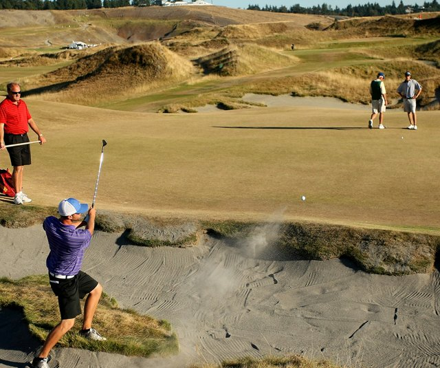Tim Peterzen blasts out of a bunker at the third hole at Chambers Bay.