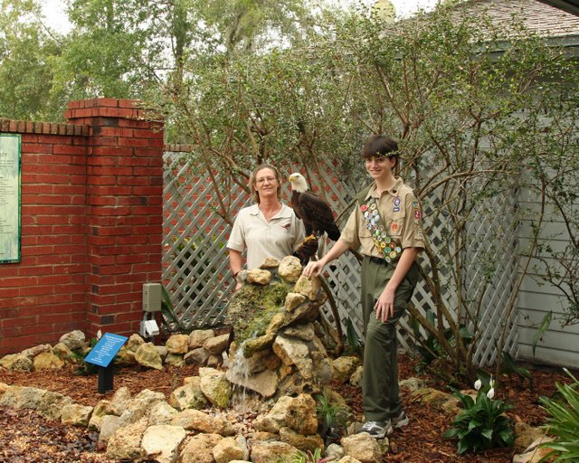 Newly named Eagle Scout Derek Donahue of Maitland, right, and Dianna Flynt of the Audubon Center for Birds of Prey pose with the rock feature Donahue's team built. Donahue is 13 and is a member of Boy Scout Troop 205 of the First Presbyterian Church.